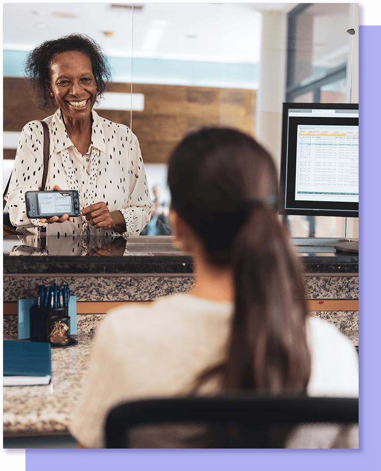 woman showing insurance card at front desk of provider