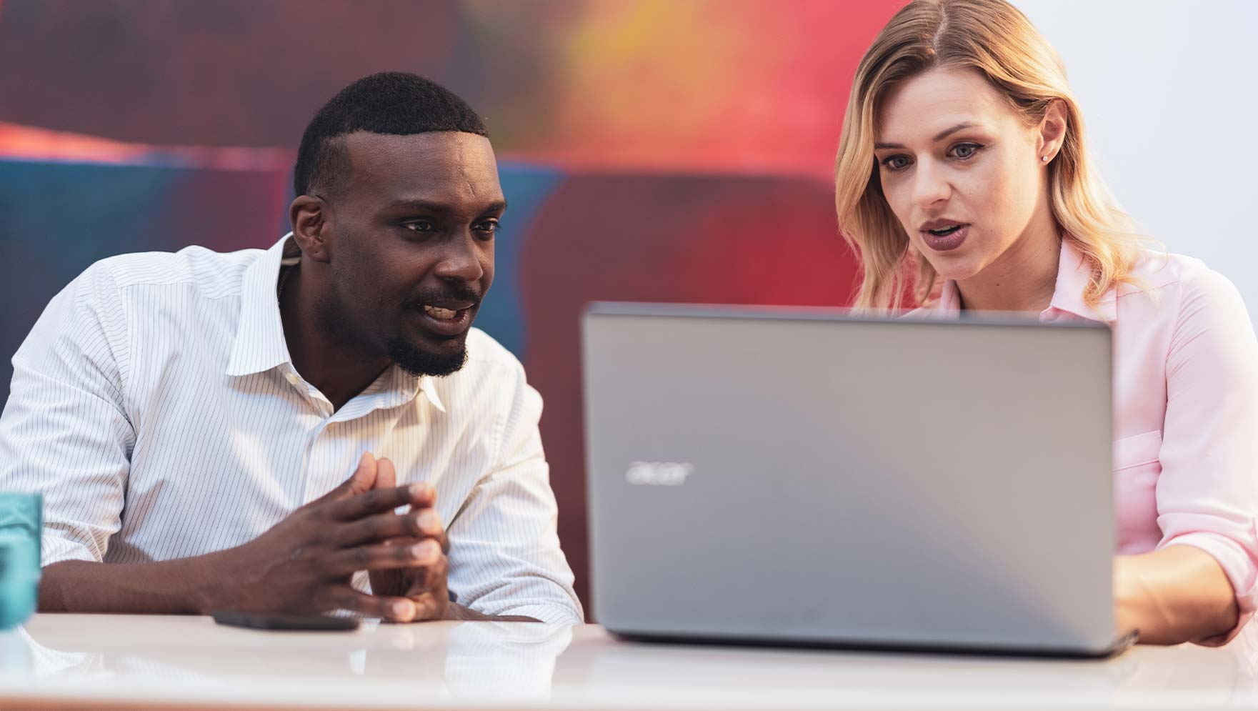 Man and woman discussing work displayed on laptop